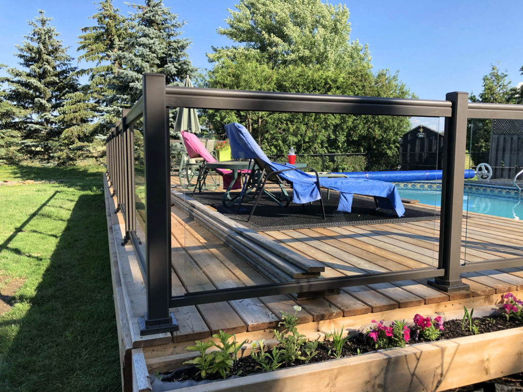 Renaissance Rail aluminum and glass railings, brown, on a backyard wood pool deck in Burlington, ON