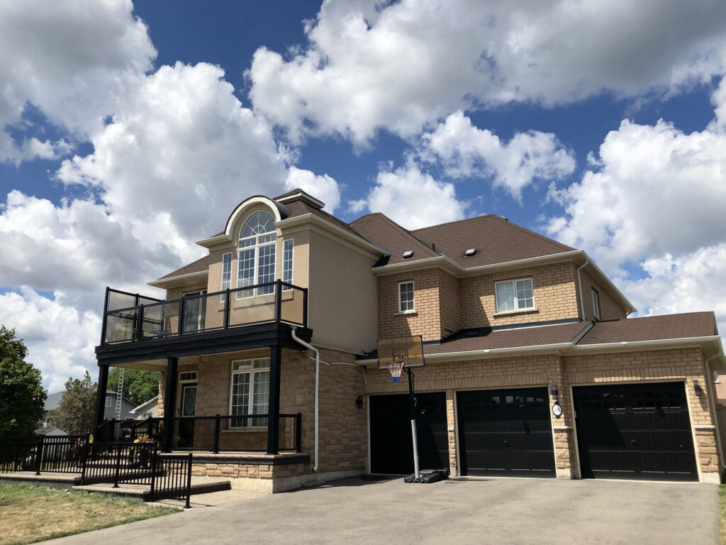 Renaissance Rail aluminum tinted glass and spindle railings, black, on a home in Grimsby, ON