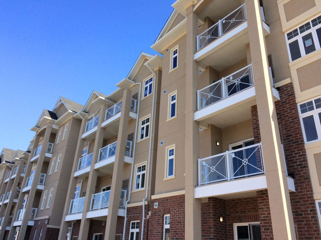 Renaissance Rail aluminum glass balcony railings, white, with Circle X-Frames, on a 4 storey residential building in Milton, ON