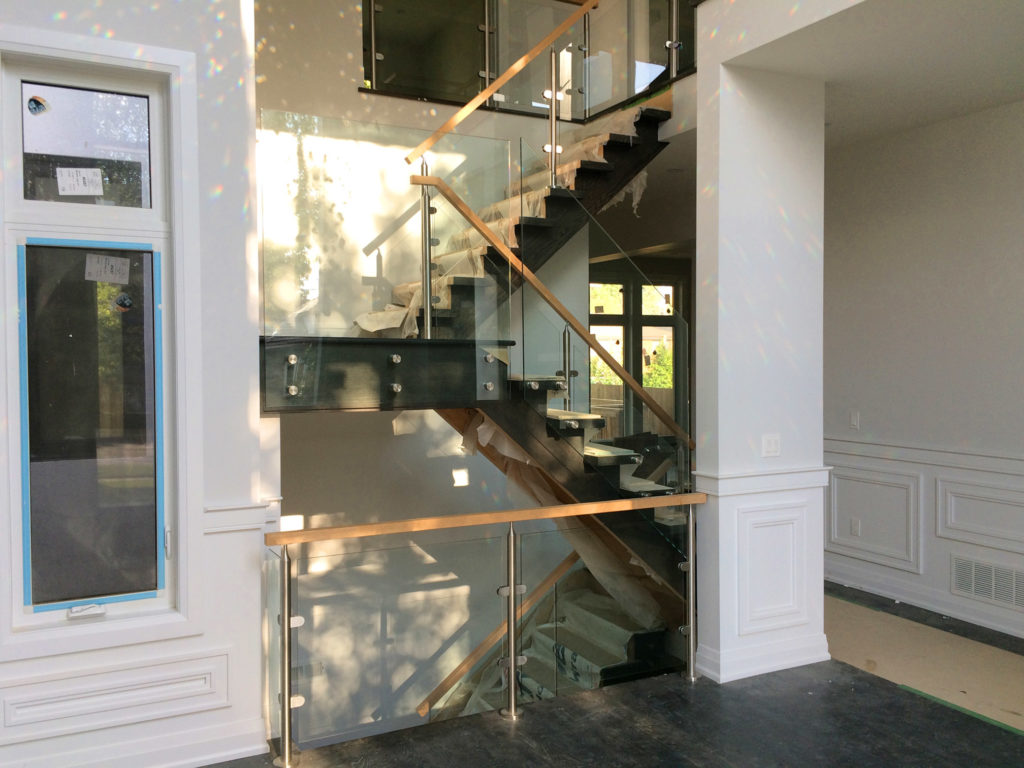 Renaissance Rail stainless steel and glass railings, standoffs and round posts, oak handrails, on interior stairs in Toronto, ON