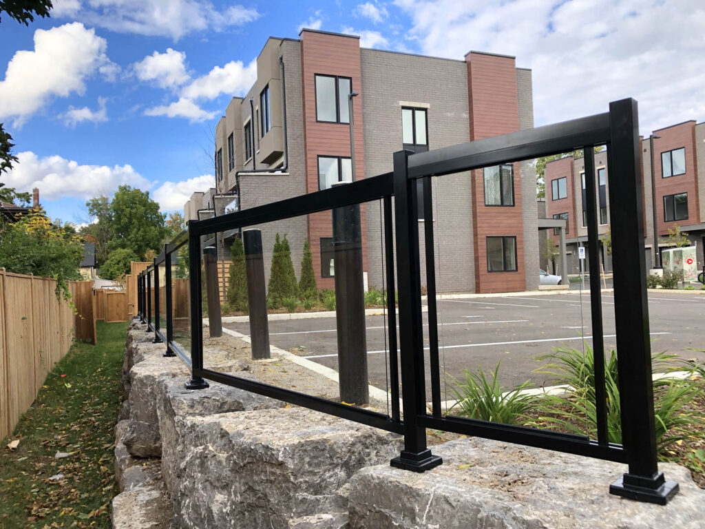 Renaissance Rail aluminum and glass railings, black, on a stone retaining wall in Cambridge, ON