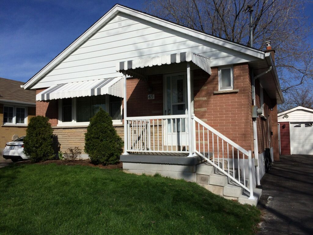 Renaissance Rail aluminum railings, white, with integrated awning support, on a front porch in Hamilton, ON